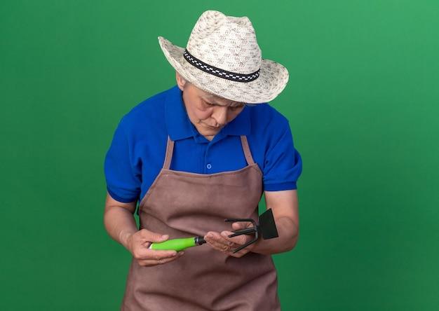 Une jardinière âgée confuse portant un chapeau de jardinage tenant et regardant un râteau à houe