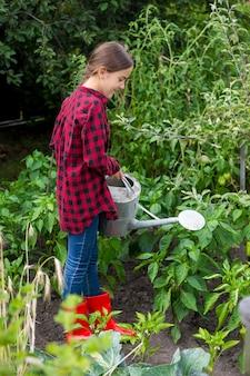 Jardinière arrosant le lit de jardin avec des légumes mûrs