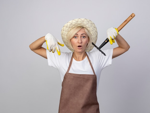 Une jardinière blonde d'âge moyen impressionnée en uniforme portant un chapeau et des gants de jardinage tenant un râteau pointant vers le bas