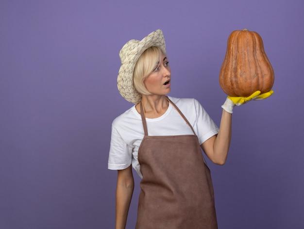 Une jardinière blonde d'âge moyen impressionnée en uniforme portant un chapeau et des gants de jardinage tenant et regardant la citrouille musquée
