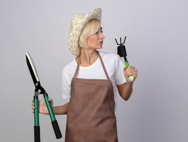 Une jardinière blonde d'âge moyen impressionnée en uniforme portant un chapeau tenant des cisailles à haie et un râteau-houe regardant de côté