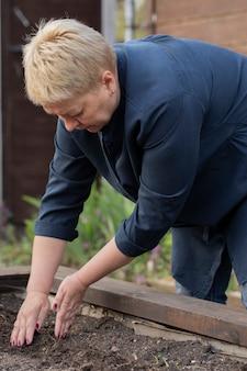 Jardinière couvre les graines avec de la terre sur le lit dans son jardin. concept de jardinage
