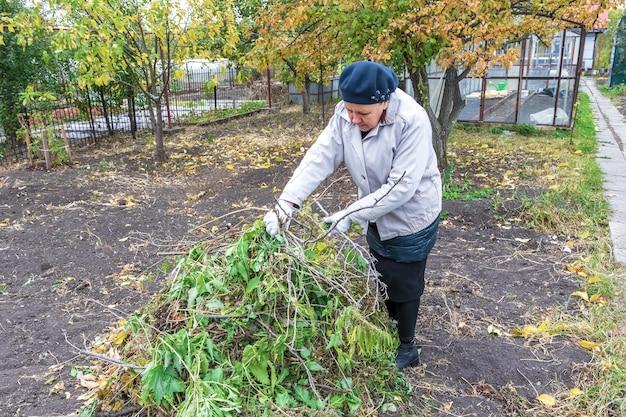 Une jardinière empile des brindilles sèches et laisse le travail d'automne dans le jardin