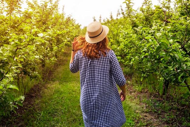 Une jardinière marche dans un verger de pommes vertes vêtue d'une robe bleue et d'un chapeau