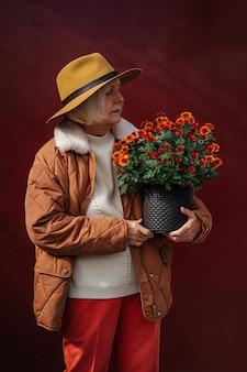 Jardinière senior en vêtements d'extérieur inspectant un bouquet de fleurs en pot sur fond vineux.