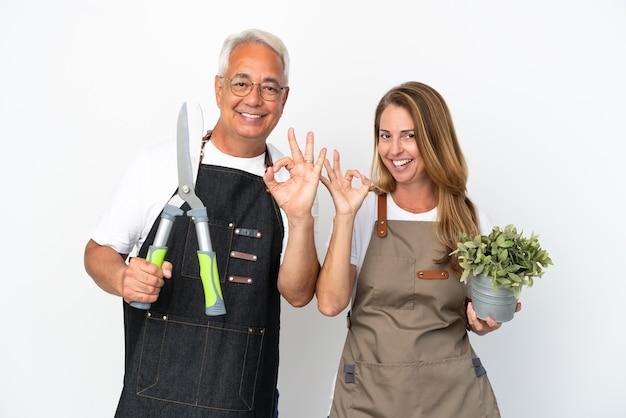 Jardiniers d'âge moyen tenant une plante et des ciseaux isolés sur fond blanc montrant un signe ok avec les doigts