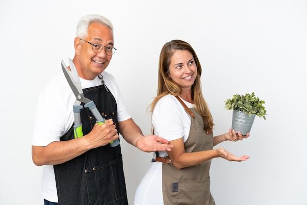 Jardiniers d'âge moyen tenant une plante et des ciseaux isolés sur fond blanc pointant vers l'arrière et présentant un produit