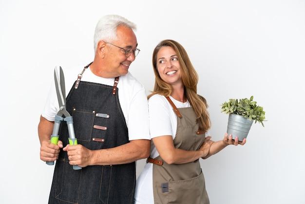 Jardiniers d'âge moyen tenant une plante et des ciseaux isolés sur fond blanc regardant par-dessus l'épaule avec un sourire