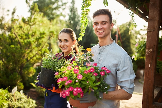 Les jardiniers heureux garçon et fille tiennent des pots avec des plantes dans de beaux jardins par une chaude journée ensoleillée.