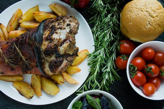 Jarret de porc frit avec pommes de terre servi sur une assiette blanche.