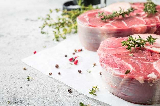 Jarret de veau frais tranches de viande de bœuf pour osso buco cuisson sur planche à découper avec ingrédients et assaisonnements poivre de thym sel