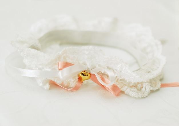 Jarretière en dentelle blanche pour la mariée avec un ruban de satin corail et un coeur doré sur fond blanc