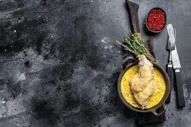 Jarrets de lapin rôtis dans une poêle avec des légumes cuits