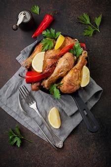Jarrets pointus du poulet frit dans une poêle en fonte sur une surface de béton sombre
