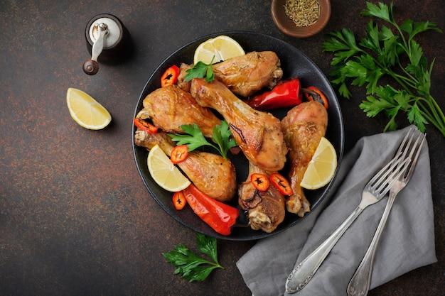 Jarrets pointus de poulet frit dans une poêle en fonte sur une surface en béton foncé ou en pierre. mise au point sélective vue de dessus.