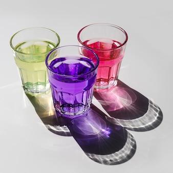 Jaune; boisson rose et violette dans des verres avec une ombre sur fond blanc