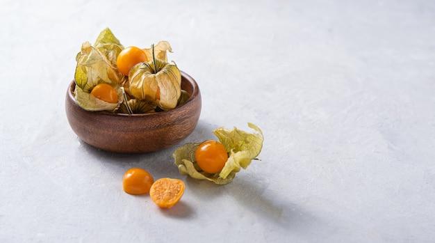 Jaune frais peruvana physalis dans un bol en bois sur fond clair. copier l'espace