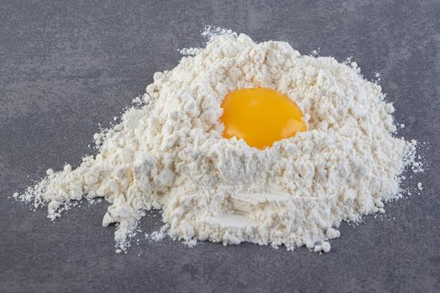 Jaune d'oeuf cru dans la farine placé sur une table en pierre.