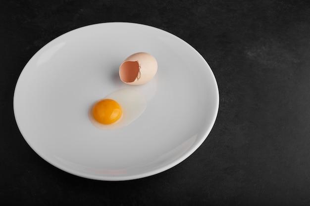 Jaune d'oeuf dans une assiette blanche avec une coquille d'oeuf autour.