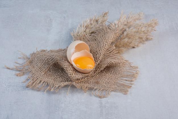 Jaune d'oeuf dans une coquille cassée sur un morceau de tissu sur une table en marbre.