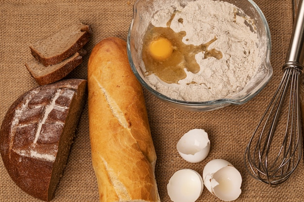 Jaune d'oeuf sur la farine. coquilles d'oeuf, baguette et tranches de pain de seigle et batteur à main sur un morceau de toile de jute. vue de dessus.