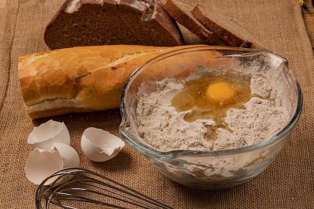 Jaune d'oeuf sur la farine. coquilles d'oeuf, baguette et tranches de pain de seigle et batteur à main sur un morceau de toile de jute.