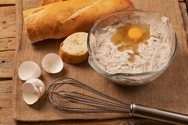 Jaune d'oeuf sur la farine. coquilles d'oeuf, tranches de baguette et batteur à main sur un morceau de toile de jute.