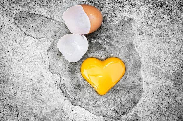 Jaune d'oeuf en forme de cœur avec des coquilles d'œuf au sol. la saint-valentin