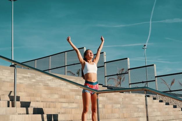 Je l'ai fait! belle jeune femme en vêtements de sport gardant les bras tendus tout en faisant de l'exercice à l'extérieur