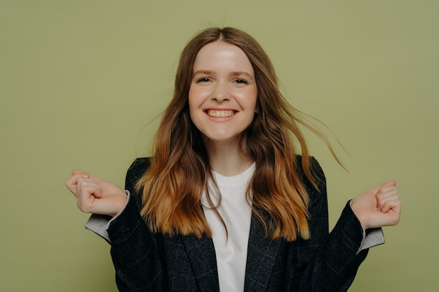 Je l'ai fait. souriante jeune femme tenant les mains en l'air démontrant son enthousiasme tout en regardant la caméra portant une veste sombre et un haut blanc, posant sur fond de studio clair. concept d'émotions humaines