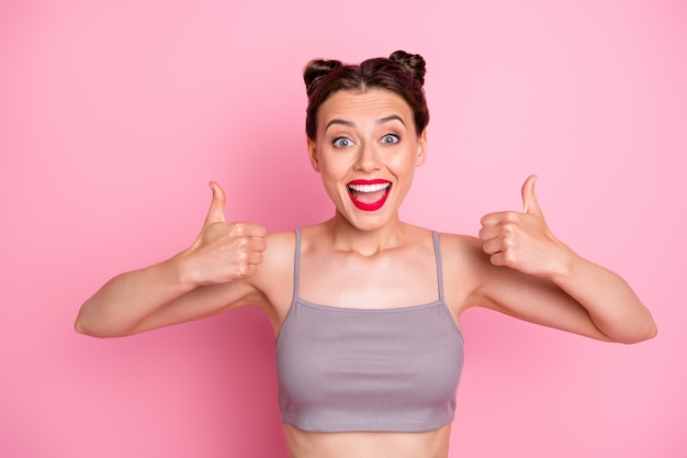 Je l'aime bien! photo de jeune fille étonnante brioches drôles soulevant les doigts du pouce exprimant le plein accord porter occasionnel gris court haut isolé couleur rose