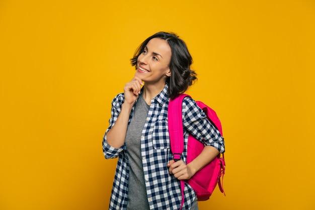 Je me demande, qu'est-ce qui m'attend? une jeune étudiante, habillée avec désinvolture, souriante et s'interrogeant sur son nouveau jour, tenant son joli sac à dos rose sur son épaule.
