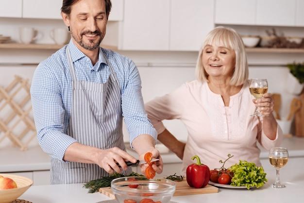 Je me soucie toujours de mes parents. heureux homme mûr heureux debout dans la cuisine et couper les tomates tandis que sa mère senior appréciant un verre de vin