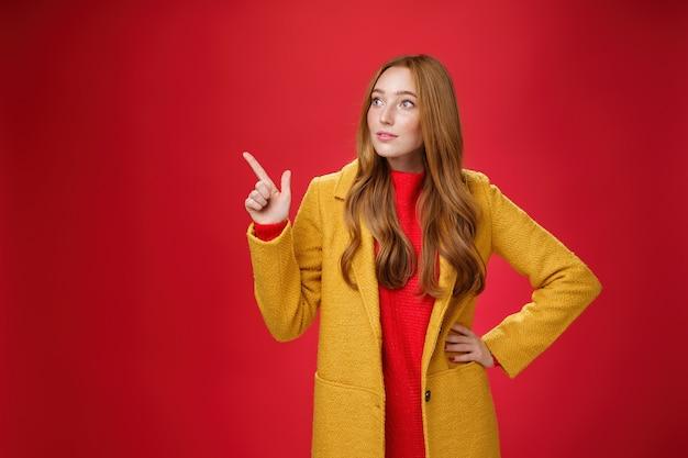 Je me suis demandé curieuse belle femme rousse en manteau s'arrêtant sur le chemin en regardant et en pointant vers le coin supérieur gauche curieuse et intéressée, observant une promotion surprenante sur fond rouge.