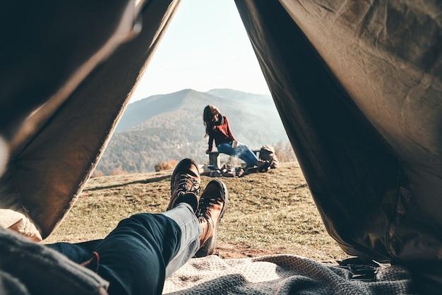 Je me suis réveillé à l'endroit parfait. jeune homme méconnaissable profitant de la vue sur la chaîne de montagnes depuis la tente pendant que sa petite amie se repose près du feu de camp