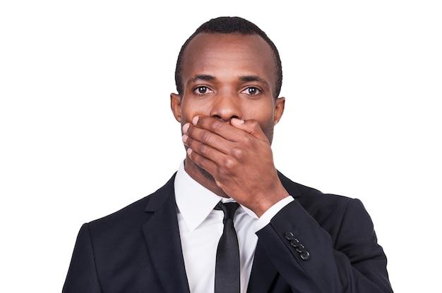 Je ne dirai rien. portrait de jeune homme africain en tenue de soirée couvrant sa bouche avec la main en se tenant debout isolé sur fond blanc