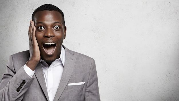Je ne peux pas croire ça! portrait de beau entrepreneur africain en tenue de soirée criant de surprise, choqué et heureux de l'accord commercial réussi, tenant la main sur sa joue avec papillon ouvert