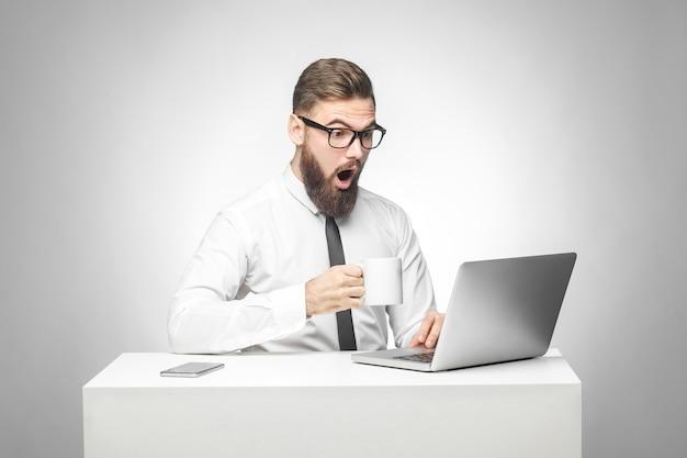 Je ne peux pas croire! portrait d'un jeune homme d'affaires choqué en chemise blanche et cravate noire assis au bureau, lisant des nouvelles et travaillant à distance avec de grands yeux surpris regardant un ordinateur portable. isolé