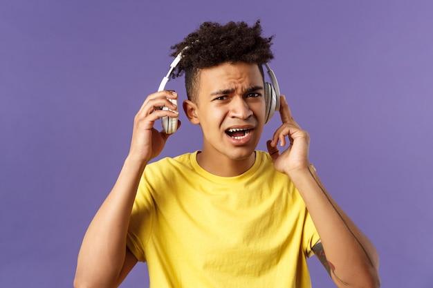 Je ne peux pas vous entendre, répétez s'il vous plaît. portrait de jeune mec dérangé interrompu d'écoute de musique, décollage des écouteurs pour répondre à la question de la personne, plissant les yeux confus,