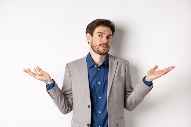 Je ne sais pas. homme d'affaires désemparé en costume, haussant les épaules et l'air inconscient, n'en ai aucune idée, debout sur fond blanc.