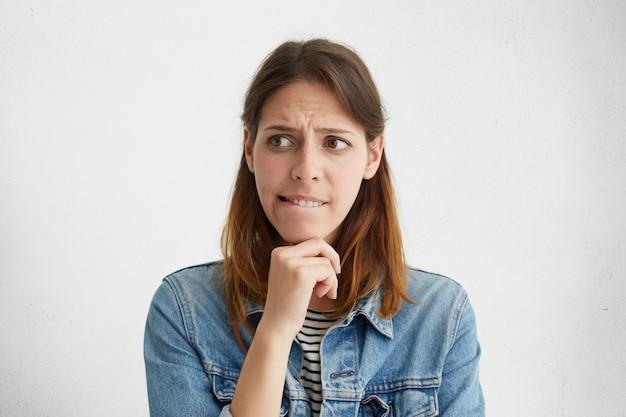 Je ne sais pas jolie femme dans des vêtements décontractés tenant la main sous le menton mordant la lèvre à côté tout en décidant quoi faire.