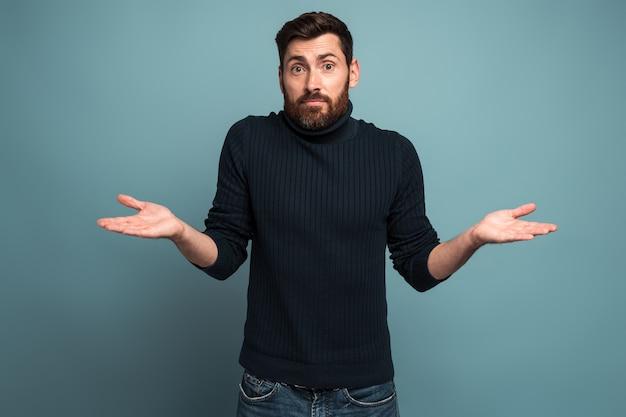 Je ne sais pas. portrait de confus beau jeune homme barbu debout avec les bras levés et regardant la caméra avec réponse. studio intérieur tourné, isolé sur fond bleu