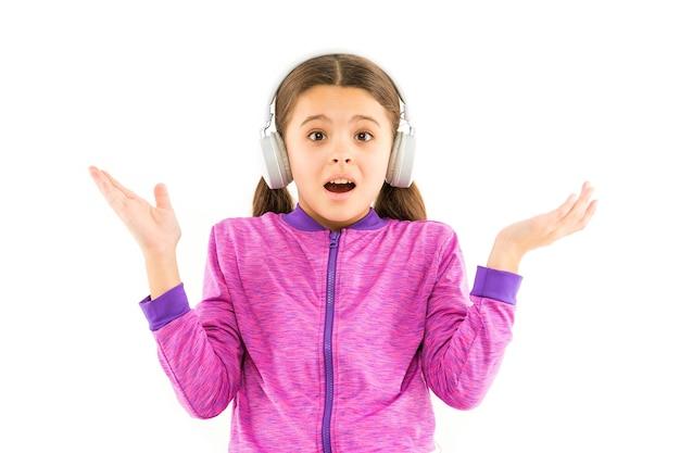 Je ne t'entends pas, la musique joue dans mes écouteurs. mélomane surpris isolé sur blanc. petite fille écoutant de la musique avec la bouche ouverte. seulement de la musique rien d'autre.