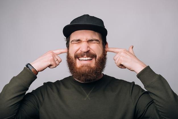 Je ne veux pas l'entendre le geste est fait par un homme qui couvre les oreilles avec les doigts.
