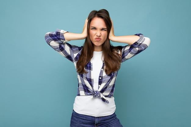 Je ne veux pas l'entendre. jeune belle femme brune insatisfaite émotionnelle portant une chemise à carreaux isolée sur bleu