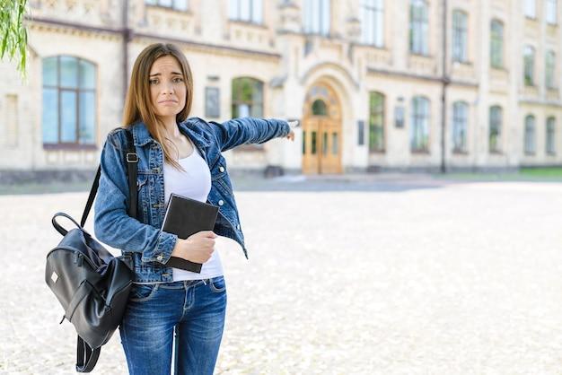 Je ne veux pas retourner à l'école ! aider! portrait photo de triste bouleversé frustré déprimé timide maladroit horrifié jolie jolie fille mignonne montrant sur les portes de la salle de classe floue fond automne