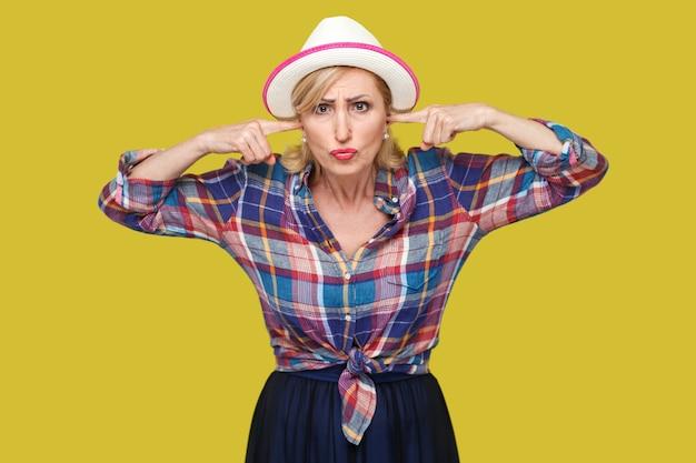 Je ne veux pas t'entendre. portrait d'une femme mûre élégante et moderne sérieuse dans un style décontracté avec un chapeau blanc debout, mettant le doigt dans les oreilles et regardant. studio intérieur tourné isolé sur fond jaune.