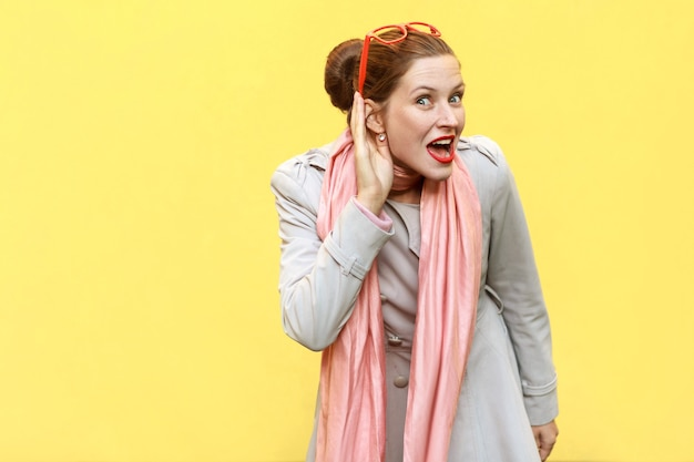 Je ne vous entends pas. belle fille rousse. prise de vue en studio, fond jaune. prise de vue en studio