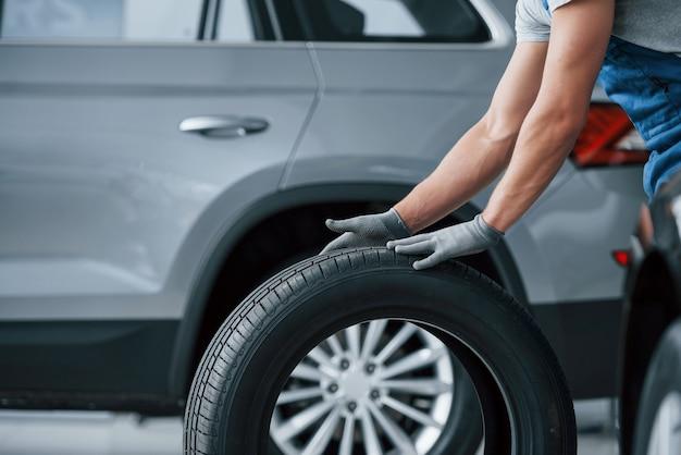 Je reviens tout de suite. mécanicien tenant un pneu au garage de réparation. remplacement des pneus hiver et été.