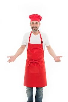 Je sais que je suis un chef cuisinier. homme mûr barbu en toque et tablier. cuisinier principal avec barbe et moustache portant un tablier à bavette. chef cuisinier mature en tablier de cuisine rouge. cuisine à la maison.